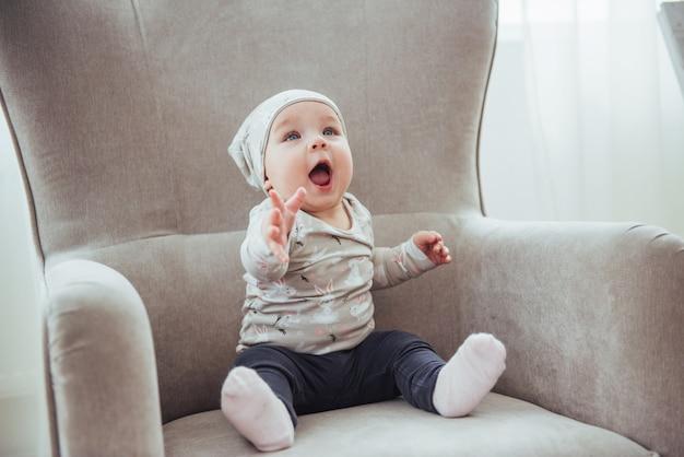 部屋のビンテージの椅子に座って、スタイリッシュな服を着ている1歳の女の子。
