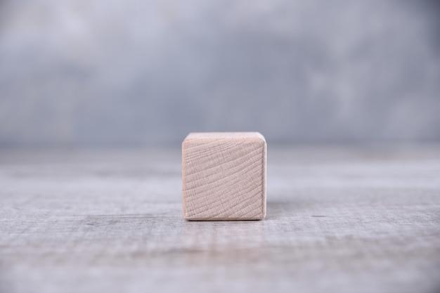 テーブルの上の単語、手紙、記号のためのスペースを持つ1つの空白の木製キューブ。テキストのための場所、無料のコピースペース