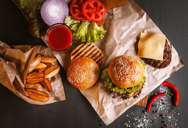 木製のテーブルに美味しい新鮮な自家製ハンバーガー。ハンバーガー、木製トレイ、フライドポテト、唐辛子のコンポーネントの隣。グラス1杯のトマトジュース