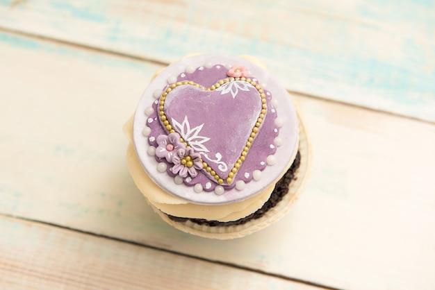 木製のテーブルに心で1つのカップケーキ