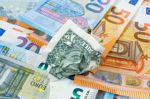 1つのしわくちゃの米ドルは新しいユーロ紙幣にあります。コンセプトは新旧です。現金の権利放棄。為替。お金は紙です。