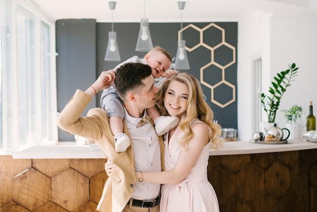 美しい若い親はパステルカラーの美しいインテリアで自宅で1歳の子供と笑顔します。家族の外観。ハッピーバースデーパーティー