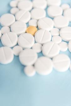 1つの黄色い錠剤で白い錠剤のクローズアップ