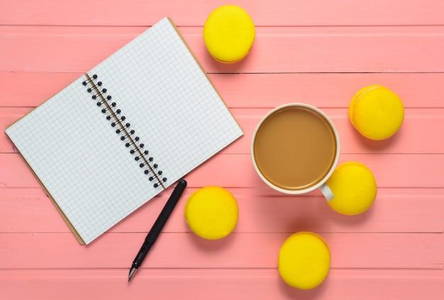 ペン、コーヒー1杯とピンクの木製テーブルの上の黄色のマカロンとノート。上面図。フラット横たわっていた。