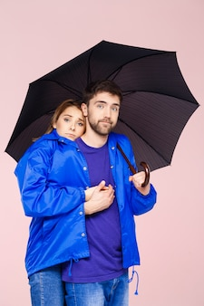 薄ピンクの壁の上に傘を保持している1つのレインコートを着てポーズ美しいカップル