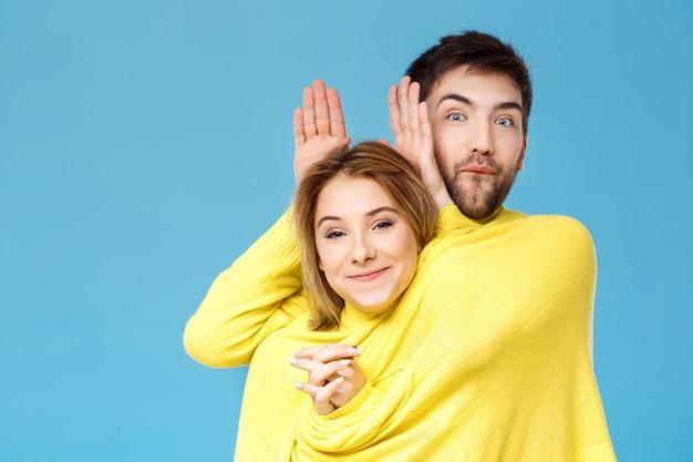 青い壁を越えて楽しんで笑ってポーズ1つの黄色いセーターの若い美しいカップル