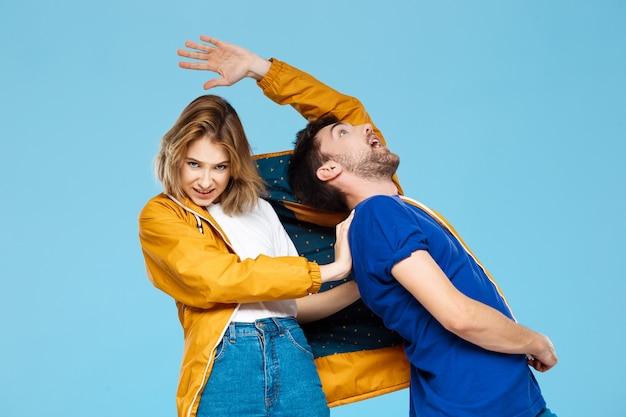 青い壁に1つのジャケットを着て面白い若い美しいカップル