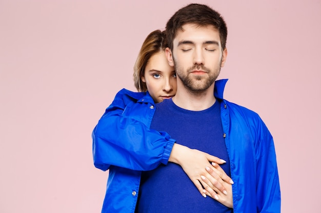 明るいピンクの壁に笑みを浮かべて抱きしめる1つのジャケットを着て面白い若い美しいカップル