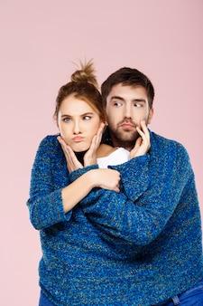 明るいピンクの壁を越えて楽しんで笑ってポーズをとって1つの青いニットセーターの若い美しいカップル