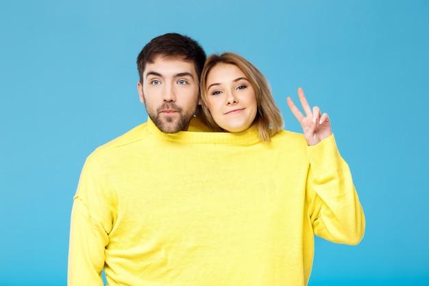 水色の壁でポーズ1つの黄色いセーターの若い美しいカップル