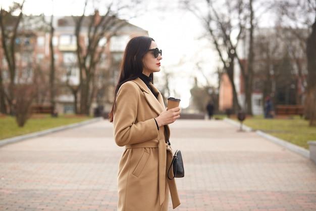 ファッショナブルなブルネットの女性は、町を散歩して1日を過ごします。