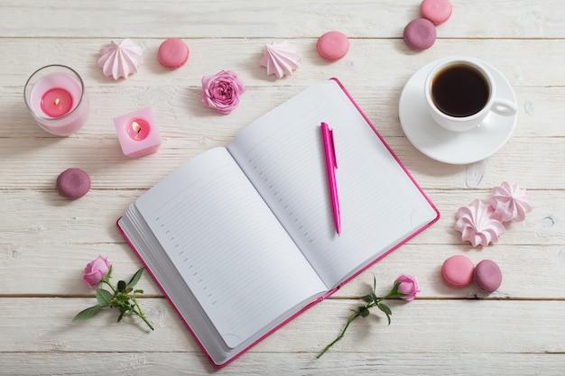 白い木製のテーブルの上にコーヒーを1杯ノート