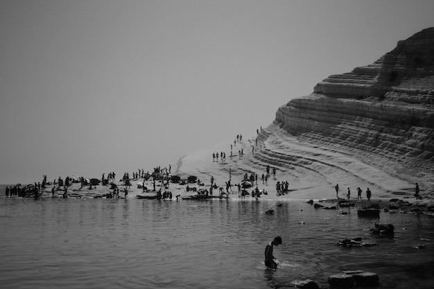 岩が多い丘の近くのビーチで1日を楽しむ人々