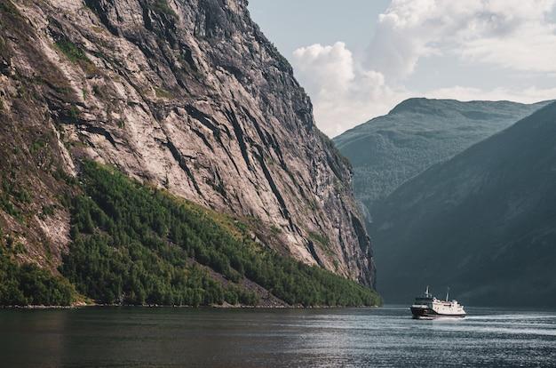 ノルウェーの曇り空の下で高い岩山に囲まれた湖で1隻の船