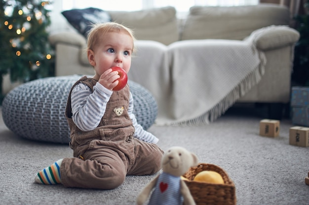床に座っているかわいい1歳の男の子の肖像画。