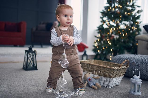 床に立っているかわいい1歳の男の子の肖像画。