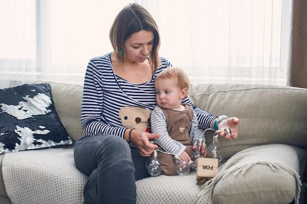 自宅のソファーに座っている1歳の赤ちゃんと母親