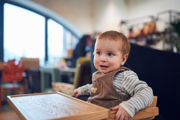自宅の木製の高い椅子に座っている1歳の男の子