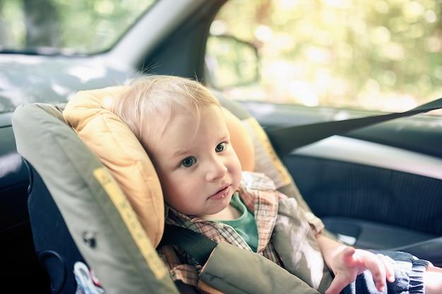 フロントシートに取り付けられた車の安全シートに座っているかなり1歳の幼児男の子の肖像画。