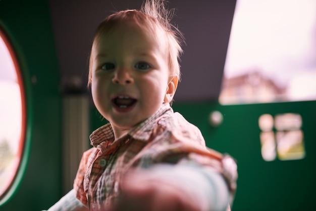 遊び場で遊んで幸せな1歳の幼児。