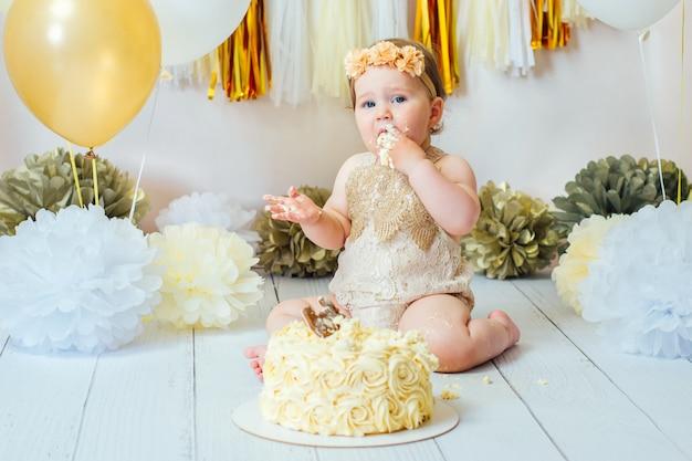1歳の女の子が最初の誕生日ケーキのスマッシュパーティーでケーキを食べる。