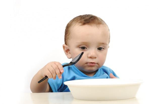 テーブル、スプーン、プレートで食べる緑の目でかわいい愛らしい1歳の赤ちゃん