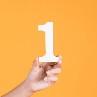 番号を1つの紙の切り欠きを持っている女性の手のクローズアップ