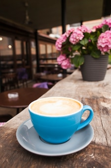 空のカフェで古い木製の織り目加工テーブルの上にコーヒーを1杯