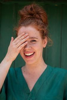 1つの目を覆っているうれしそうな赤毛の女性