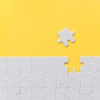 黄色の背景に1つの行方不明のパズルのピース