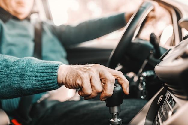 彼の車に座っている間ギアシフトとステアリングホイールに他の1つの手を保持している年配の男性人のクローズアップ。