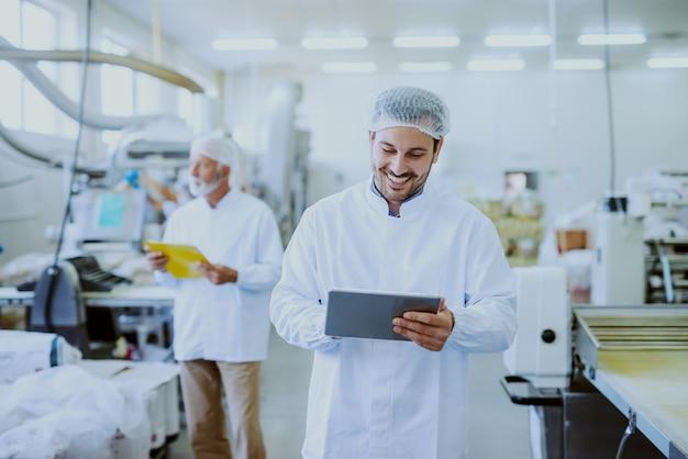 食品工場に立っている間タブレットを使用して滅菌した白い制服を着た若い白人笑顔スーパーバイザー。バックグラウンドでは、マシンを制御する古い1人のワーカー。