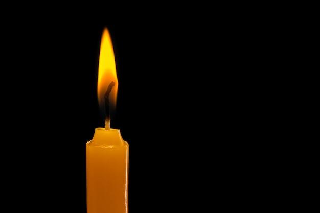 1つの明るいろうそくが燃えています。スタジオ撮影で分離黒