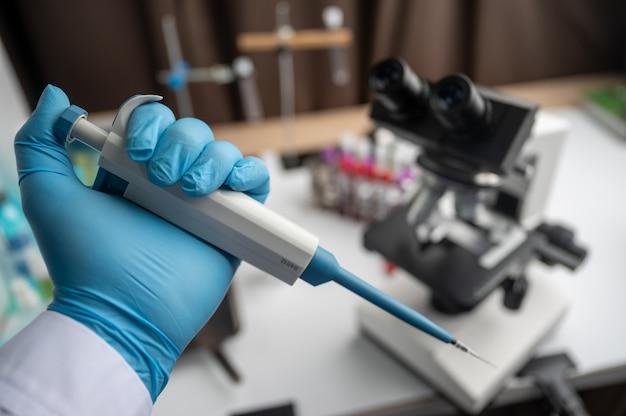 医療機器血液検査。いくつかの試験管の1つに液体を加えるピペット