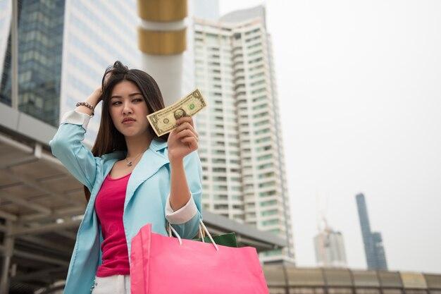 悲しいセクハラのアジアの女の子は手元に1ドル紙幣を見る