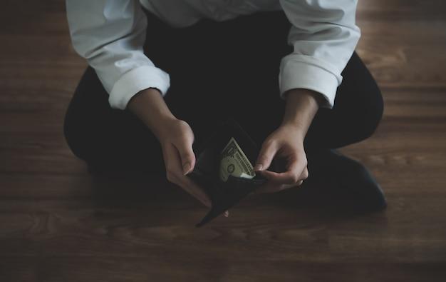 ビジネスマンは、1つの米ドル紙幣で開いている財布に座って彼のビジネスに財政上の問題と失敗があります。