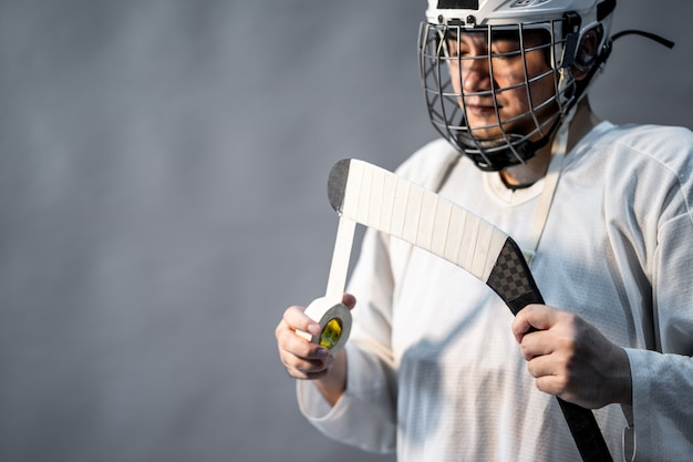 プロのアイスホッケー選手暗い部屋で怒っている、1つの照明を感じる。