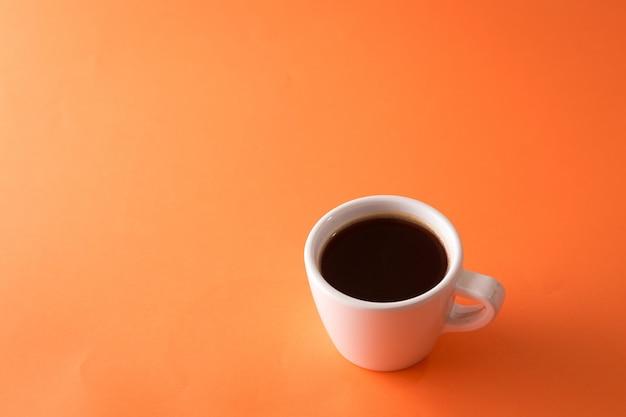 オレンジ色の背景上のコーヒー1杯