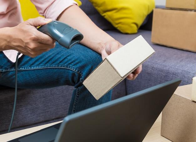 バーコードスキャナーを使用してオンライン商品の男性が商品ボックスの1つをスキャンする