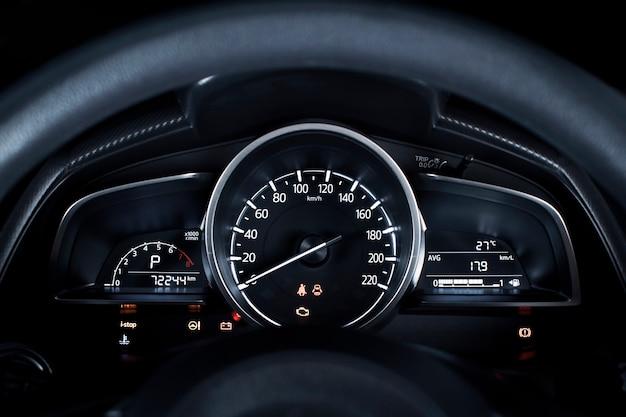 1時間あたりのキロメートルおよびタコメーター、燃料計、走行距離計および車のダッシュボードの警告灯が付いている車の速度計。