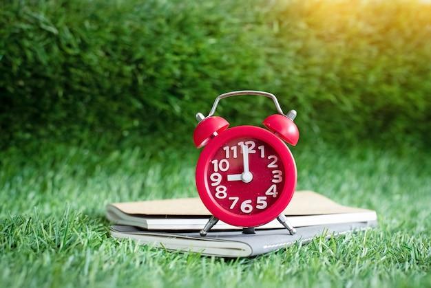 目覚まし時計と本は緑の芝生の1階に置かれ、周りにぼやけた光が