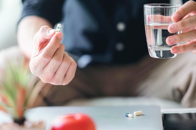 トリミングされた男性の画像は、自宅の居間に座って錠剤とコップ1杯の水を保持しています。