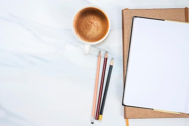 空白のページのノートブック、鉛筆、白い大理石のテーブル背景にコーヒー1杯のトップビュー