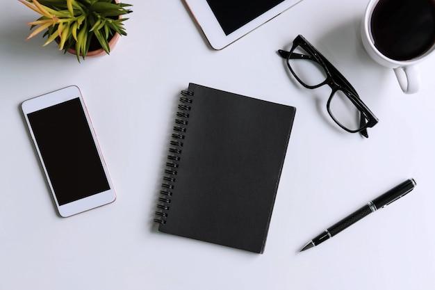 空の画面スマートフォンとコピースペースを備えたビジネスデスクオフィスのコーヒー1杯とタブレット