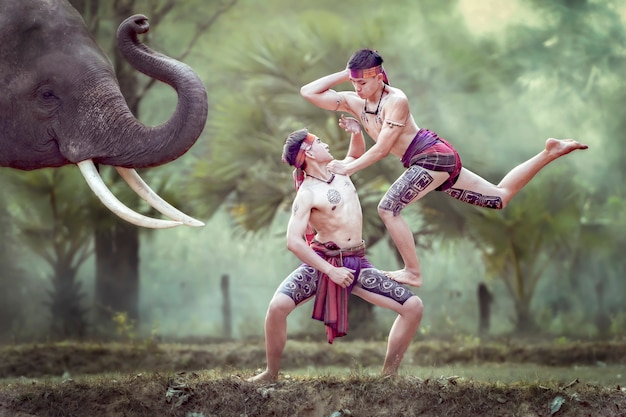 タイ人の芸術の1つである象の前で古代のボクシングダンスを練習しているタイの男の子。