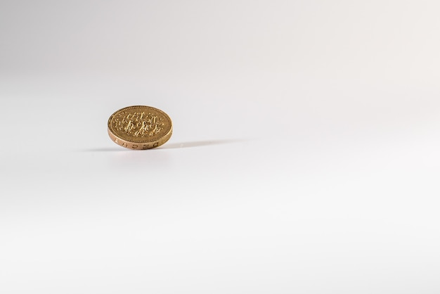 分離された、白い背景の上に落ちる1イギリスポンド硬貨
