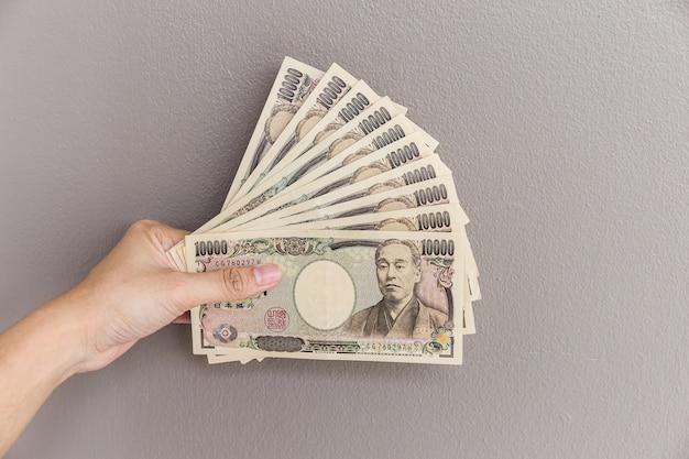 灰色の壁に1万円のお金を手にしてお金を与えている実業家