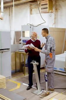 家具工場で立って話し合いをする男性、そのうちの1人は身体障害者