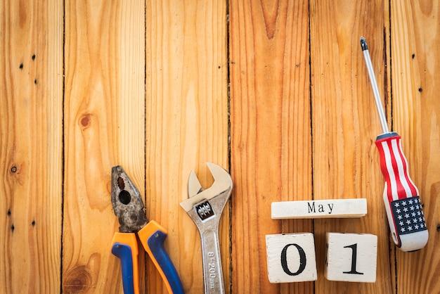 Деревянный блок календарь на день труда, 1 мая. многие удобные инструменты на деревянном фоне.