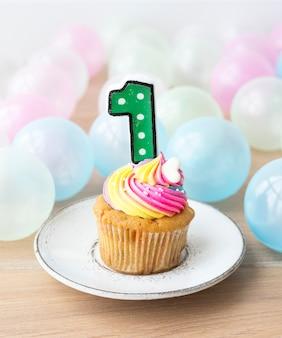 数字の1つのキャンドルとカラフルなカップケーキ